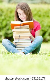 beautiful and happy young student girl sitting on green grass, pile of books under her hands, smiling and reading book. Summer or spring green park in background