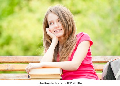 beautiful and happy young student girl sitting on bench, her hands on pile of books, looking away from the camera, smiling and daydreaming. Summer or spring green park in background