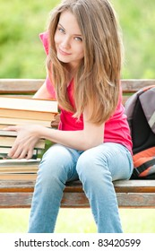 beautiful and happy young student girl sitting on bench and lifting heavy pile of books with her hands, smiling and looking into the camera. Summer or spring green park in background