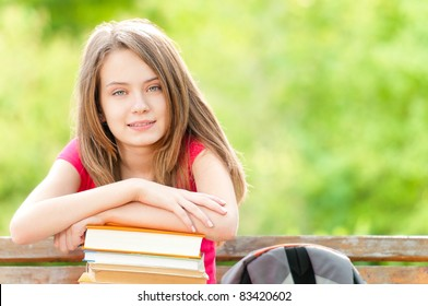 beautiful and happy young student girl sitting on bench, her hands on pile of books, looking into the camera and smiling. Summer or spring green park in background