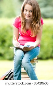 beautiful and happy young student girl sitting on pile of books, holding exercise book in her hands, smiling and looking into the camera. Summer or spring green park in background