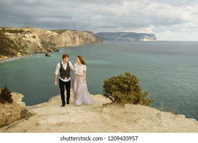 beautiful happy young wedding couple are standing on the mountain with sea