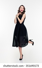 Beautiful happy young woman in black dress and shoes with bright makeup in retro style over white background