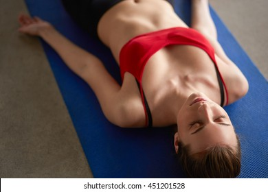 Beautiful happy young woman in bright sportswear lying down indoors on blue mat. Girl staying in Shavasana Corpse or Dead Body Posture, resting after practice, meditating, breathing