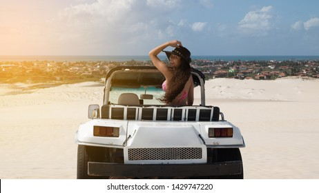 Beautiful happy young woman with buggy ride through the dunes of the coast of Brazil.