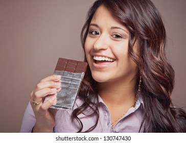 Beautiful happy young woman with chocolate bar