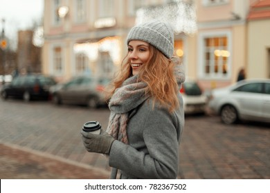 Beautiful happy young woman with a cup of coffee in a vintage fashion gray winter coat with a knitted fashionable cap and a stylish scarf walking in the city
