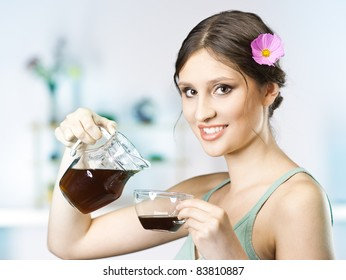 beautiful happy young woman drinking tea in the kitchen