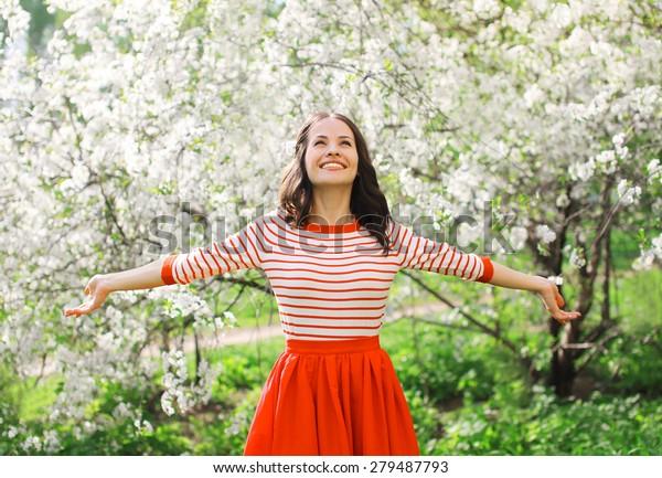 花の咲く春の庭で香りを楽しむ美しい幸せな若い女性