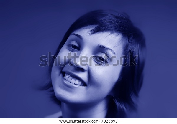 Beautiful happy young woman face. blue tone mode