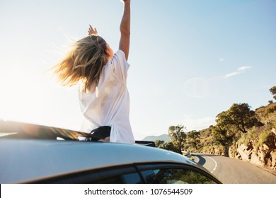 Beautiful and happy young woman, full of emotions and feelings enjoys warm summer air and sunshine on sunny day, stands up in car out of convertible cabriolet, wind in hair full of freedom