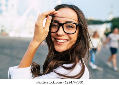 Beautiful happy young woman in glasses having good time on city square while walking outdoors