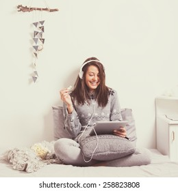 Beautiful happy young woman with headphones and tablet watching a movie on tablet in bed eating popcorn. Mild retouch, matte color filter, contemporary look.