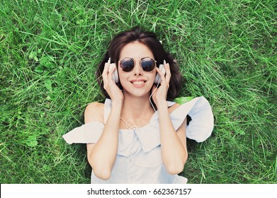 Beautiful happy young woman with headphones listening music lying on grass. Summer girl portrait