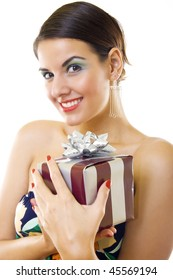 Beautiful happy young woman holding a gift over white background