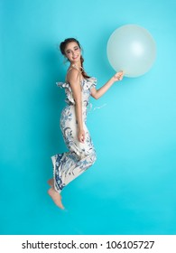 beautiful, happy, young woman jumping with an inflatable balloon in her hand