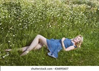 The beautiful happy young woman lies in the field of chamomiles