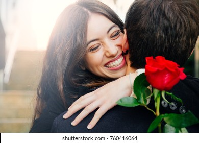 Beautiful and happy young woman in love hugging her boyfriend holding a red rose