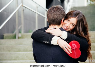 Beautiful and happy young woman in love hugging her boyfriend holding a red heart shaped gift box
