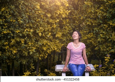 Beautiful happy young woman lying on a Garden in the summer park and smiling. Holidays, vacation