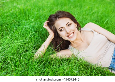 Beautiful happy young woman lying on grass, summer girl portrait