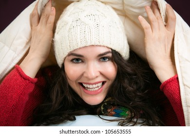 A beautiful happy young woman peeking out from underneath the blankets of her bed