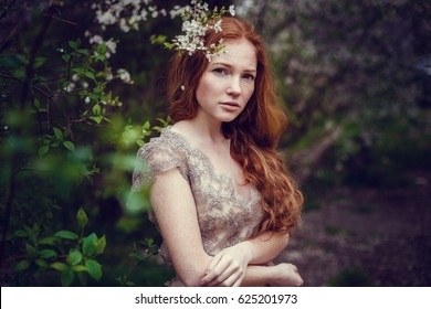 Beautiful happy young woman with red hair enjoying smell in a flowering spring garden.