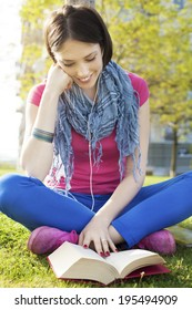 Beautiful happy young woman sitting on grass, enjoy sunny day and listening music with headphones while reading book.