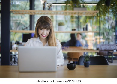 Beautiful happy young woman sitting in cafe and using laptop