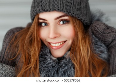 Beautiful happy young woman with a smile in the winter knitted hat and mittens vintage.