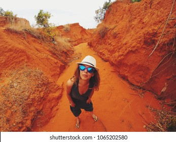 Beautiful happy young woman standing on Red sand dune. POV Angle with Action Camera