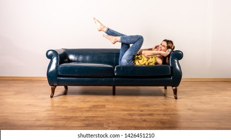 A beautiful happy young woman in a yellow dress listening to music and enjoying it while posing on a sofa.