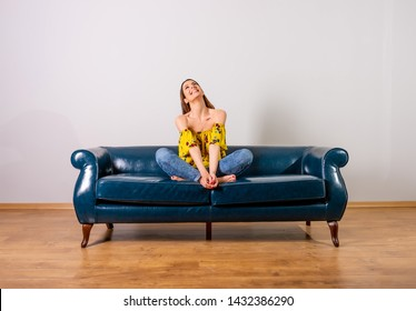 A beautiful happy young woman in a yellow dress sitting on a sofa.
