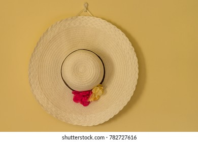A beautiful hat hanging on a wall.