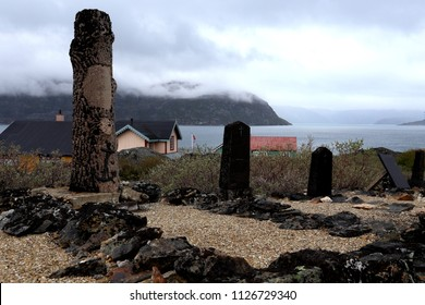 Beautiful haunting cemetery with monument to sailors and illegible tombstones in Greenland ghost mining town