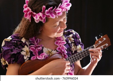 beautiful Hawaiian dancer with flowers and diverse outfit and playing ukulele, on black background