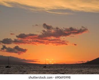 Beautiful Hawaiian Sunset at Kihei Beach on Maui Hawaii with two sail boats and clouds, deep orange, seascape