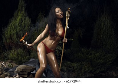 Beautiful healthy fit woman wearing red bikini & Holding burning torches. Night filming.