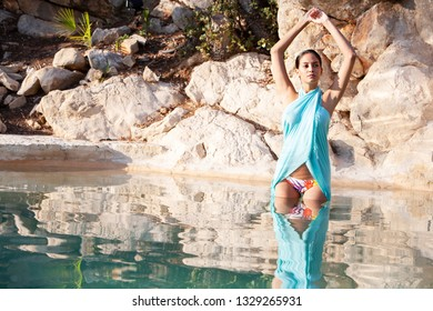 Beautiful healthy hispanic woman in natural swimming pool with reflections, doing yoga, wellness spa outdoors. Exotic female relaxing in vacation retreat, leisure recreation lifestyle, beauty travel.