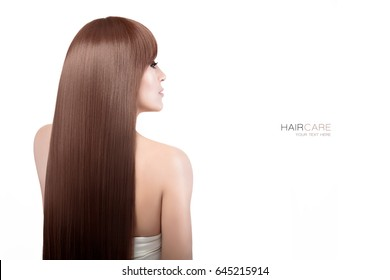 Beautiful healthy long hair.  Beauty brunette model with gorgeous straight long hair hanging down her back turning to look to the side towards copy space, isolated on white. Smooth straight hairstyle