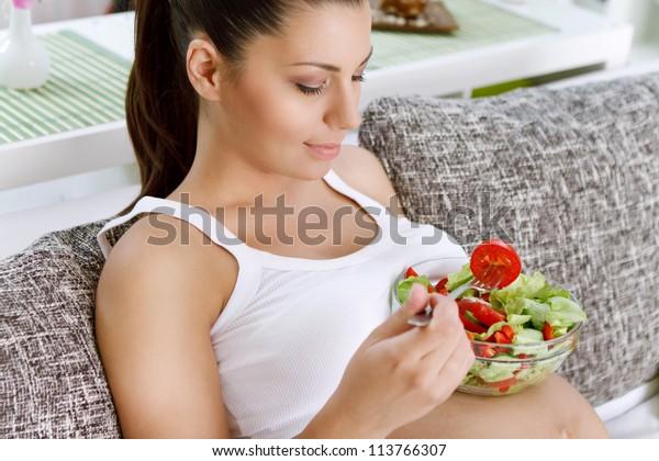 Beautiful healthy pregnant woman  eating vegetable salad