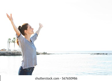 Beautiful healthy serene woman relaxing contemplating the sea on a beach, raising arms up and breathing fresh air, outdoors. Wellness, health and well being lifestyle. Recreation sunny exterior.