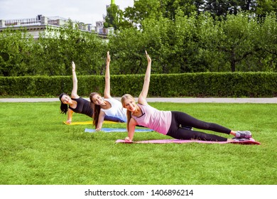 Beautiful healthy slimy young women doing exersices on the green grass in the park, side strap plank with hands up, looking at camera with toothy smile.