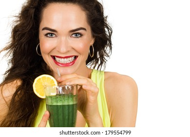 Beautiful healthy smiling woman holding and about to drink an organic green smoothie. Isolated on white.