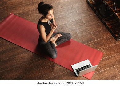 Beautiful healthy woman doing yoga exercises while sitting on a fitness mat at home, using laptop computer, stretching