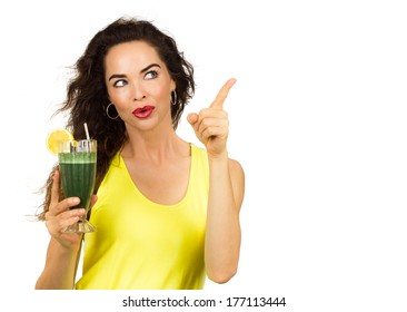 Beautiful healthy woman holding an organic green smoothie and pointing at copy-space.  Isolated on white.