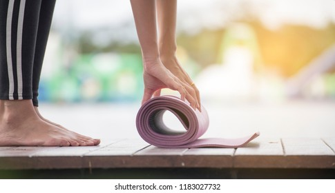 Beautiful Healthy woman rolling yoga mattress after doing yoga beside a swimming pool. Relaxation happiness Healthcare concept.