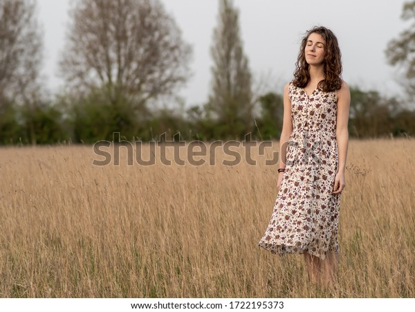 Una hermosa y saludable joven bailarina vestida de forma pacífica medita y piensa en un campo de césped marrón al atardecer