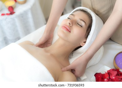 beautiful and healthy young woman relaxing with face and shoulder massage  at beauty spa salon