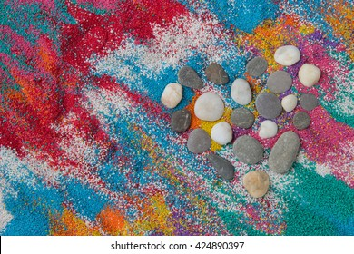 Beautiful heart background on colored sand made from seashells of different shapes and stones